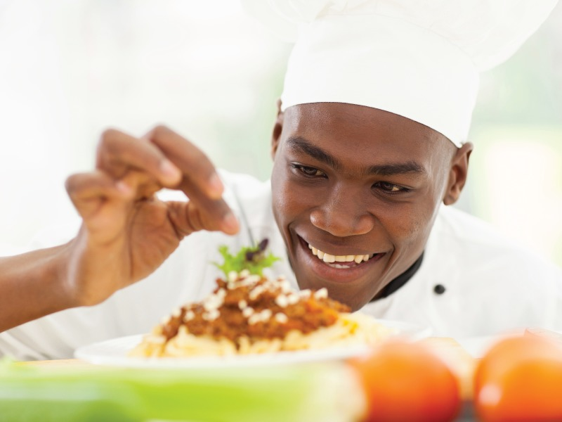 Chef putting the finishing touches on a pasta meal ready to be served.